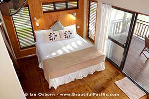 king bed of beachfront villa as seen from mezzanine